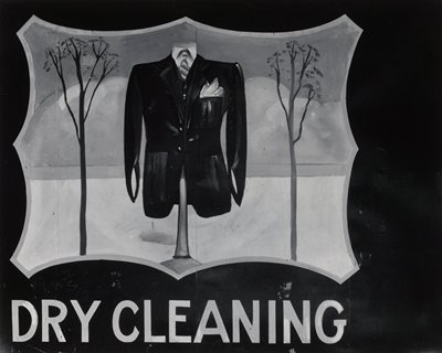 "photo of hand-painted sign with man's suit on a form, flanked by thin trees; ""DRY CLEANING"" below"