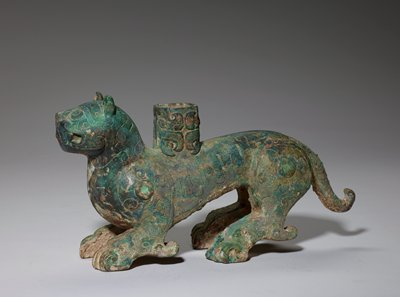 The decor of incised lines and spirals on this animal recall those on the Middle Chou water buffalo, Karlgren Number 90 (50.46.113). It should be noted, however, that the spirals on shoulders and hind quarters area here centered by a raised ring with turquoise inlay. These decor figures might point to a similar epoch were it not for certain details that are a clear indication of a later date. The rope pattern around the eyes, on the eyebrows, the fetlocks, and on the dragon decorating the socket, as well as the granulation on the front of the ears and the head of the dragon, point to the Early Huai Style Period. The socket on the back suggests that the tiger served as a podium. Patina bluish- green.