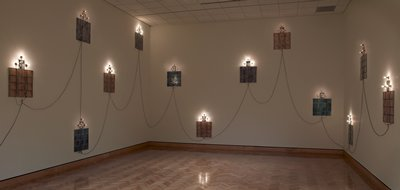 each unit consists of a vertical framed photographic portrait of a child at top center and four rows of three framed horizontal TV snow-like photographic images in tan, grey, or blue, and a set of three bulb sockets above, each socket with one light bulb, with exposed hanging electrical wiring connecting the units together; any number of units can be installed in any configuration, with the maximum number of 22 units available for installation