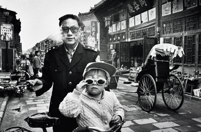 smoking man wearing glasses and a military-style jacket, standing behind a bicycle with a child wearing a sweater, cap and sunglasses; rickshaw at R; city street scene