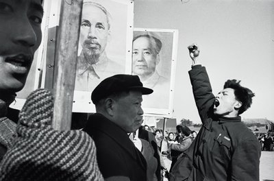man with upraised fist, shouting, at R; people holding signs, posters and flags, including sign with portrait of Mao Tse Tung, at L and R