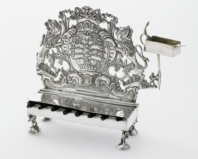 """back has openwork design with lions flanking a cartouche with a menorah; light incised lattice design on top of lamp compartment cover; tiny lions on domed feet; cover of lamp compartment detaches from the main lamp body when it is opened more than 75%, possibly due to the fact that it seems to be missing a hinge pin on the """"back left"""" hinge."""
