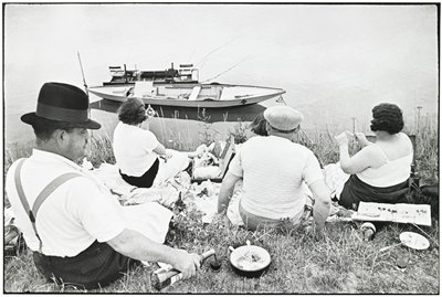 five people picnicking on a grassy shore line with two boats anchored in the water