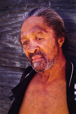 black man with grey beard, hair brushed back, open black shirt exposing bare chest; weathered gray wood backdrop