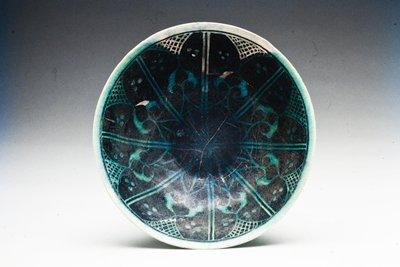 Bowl, black. Champleve design under blue glaze.; eight part design of leaf form with cross-hatching between leaf at rim.