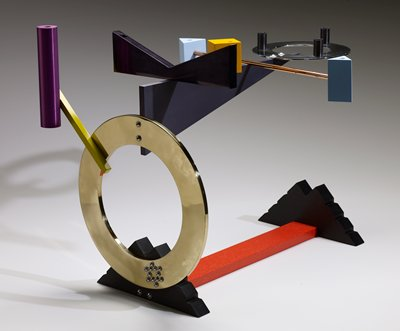 geometric designs in a variety of colors in a sculptural form; two notched black pyramid shapes on either end of red textured bar form base; large open gold ring on  one side with small yellow bar extending out on a diagonal, attached to a purple cylinder; grey triangular shaped attached to top of gold ring, topped with black double wedge shape in shiny black enamel, yellow square shape, copper-colored rod with light blue sideways pyramidal shapes, and horizontal silver ring with three black cylinders
