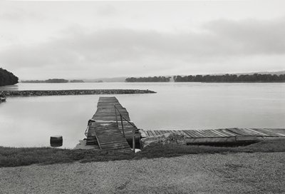 two old plank docks at right angles--one running parallel to shore--with plank ramp at front; narrow, rocky peninsula at left; trees on opposite shore at right and at horizon line; cloudy sky