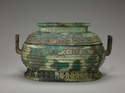 The name Su for this type of vessel is confirmed by inscriptions, the difference between a Su and a Kuei being that the former is oblong, the latter round. The lid of this Su, if inverted, will be a vessel in itself. The workmanship, unusually fine for the period, exhibits some of the most typical features of the Middle Chou Style. The foot belt presents the so-called 'wavy line,' here executed in open work; the belly has the 'grooves' (gadrooned bands); and the neck and lid belts display the 'scale band' in flat relief. In the last two areas a small flange appears in the center of the long side, thus following the Yin tradition of dividing a cessel into four panels by handles and flanges - or free animals' heads. the Yin time but ubiquitous in Chou. Inside the ring on the lid is a bottom decor in flat, double-banded relief a beg S-shaped dragon's body ending in a dragon's head at each end. To be noted, in addition to the long tongue, the ear, and the crooked horn, are the eyes in high relief just below the tufts midway on the body. Patina green with patches of blue.