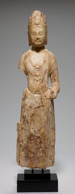 Standing Bodhisattva of white marble, right arm broken off below shoulder, left above wrist. Figure wears narrow scarf tied in x-like form at waist, and skirt whose upper edge falls over in narrow peplum effect over girdle. Elaborate jewelled necklace and heavy chains hanging to knees. High headdress. Feet missing; head restored at throat where formerly broken.