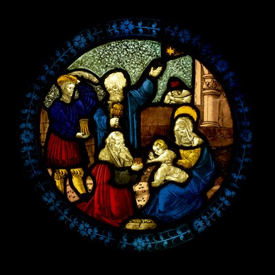 round stained glass panel depicting the Adoration of the Magi, with Mary seated at one side holding baby Jesus on her lap; three men holding gold containers at other side; central standing man gestures up to the Star of Bethlehem; angel above Mary's head; floral border