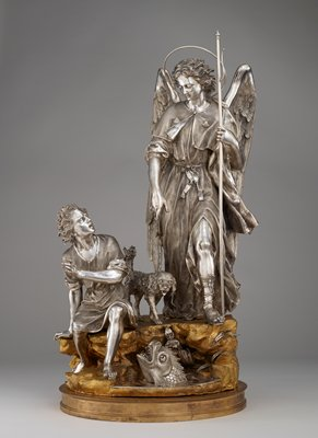 standing male angel at right with a thin wire halo and carrying a thin staff with a curved thin element on front; angel wears robe with a shell motif on each side of chest and a sash with incised flowers over his PL shoulder; angel points downward with his PR hand; young man seated on rock at left, with bare feet, wearing a short robe with zigzag design at hem, looking up at angel; fantastic fish with many teeth, tongue and snout emerging from water at center; spaniel-type dog between two man figures, looking down at fish; figures are silver, base/rocks are gilded