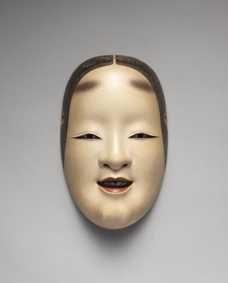 mask of a slightly smiling female face; lips slightly parted with black teeth; eyes looking straight forward; painted eyebrows near top of forehead; painted black hair framing face; ivory pigment with gray shading