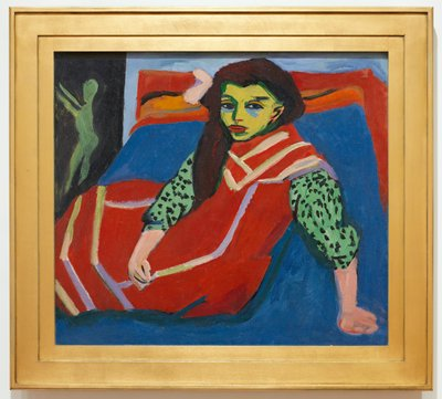 Seated girl. Franzi Fehrmann. German Expressionism. Figure shown nearly full length, filling almost all of the picture space, seated on vivid blue divan dressed in bright red dress with yellow trim and black polka dots on green sleeves. Small nude figure at left a frequent motif in Kirchner's art. Strong color utilized, applied in broad areas with an eye to contrast and balance. Harsh contour lines add a decorative element to the composition. These strong contour lines reveal the influence of the woodcutting technique which Kirchner also practiced to great effect. Composition is simplified and economy of line and form reveal influence of Japanese art and primitive African sculpture. No signature - checked 8-21-96.