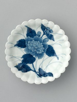 small plate with scalloped edges; blue underglaze design of a fully blossoming peony with leaves and buds; thin grass sprays in background; elevated on foot; bar design on foot; stylized leaf design outside