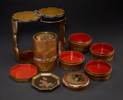 picnic set with four stacking bowls decorated with bands of flowers and foliage from each of the four seasons; sake flask created from bamboo, with bamboo leaf motif and crested flying birds; sides of caddy are decorated with wisteria; lid for stacking bowls features phoenix with chrysanthemum design; silver handle