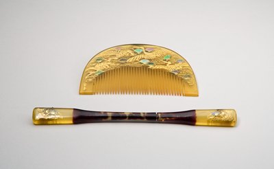 comb with four flying cranes across top between stylized pine boughs that resemble fans, in mother of pearl