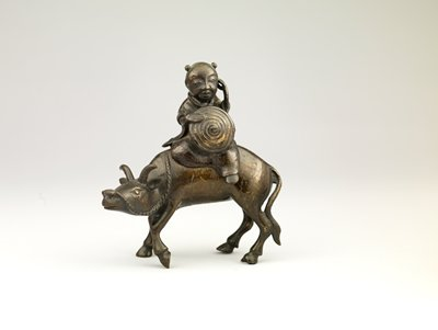 figurine of a boy riding side saddle on a water buffalo; boy is holding a shield with a swirl pattern in PR hand while holding PL hand up to his own ear; water buffalo holds its head slightly down in walking pose