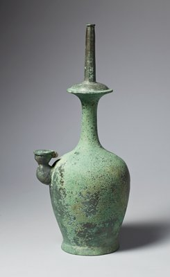 pitcher with very narrow neck with decorative disk within neck, and narrower, needle-like mouth; short, squat, segmented spout with loose cap; thin incised lines around soft shoulder; green patina