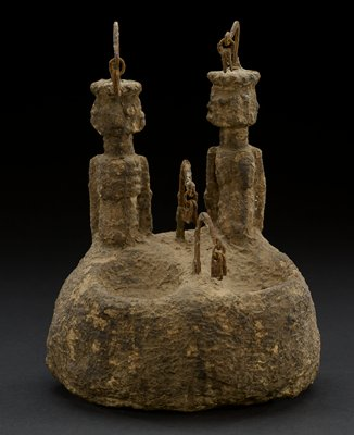 rounded lower portion/base, with two rounded indentations at front top; two figures from the torso up, with arms at their sides, behind indentations--female figure at right, male figure at left; each figure wears a flat headdress with scalloped edges with a rounded metal hook extending up from top center, with a pair of pendants hanging from each hook; two more similar hooks with pendants on base--one between figures, one between indentations; heavy; piece is encrusted overall--facial features of figures blurred by encrustations; brown patina