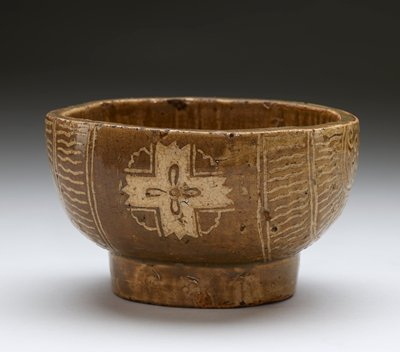 ovoid shaped vessel with slightly squared-off corners; raised ovoid foot ring; incised decorations on exterior with cross on either long side with flower-like design at center and looping lines connecting arms of cross, which are zig-zagged at ends; short ends decoration with radiating sun-like designs with looping swirls at center; designs are inlaid with white glaze or slip; greenish-grey glaze; interior has parallel incised lines