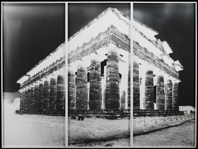 negative image of classical building with thick fluted columns; fence with X shaped panels in foreground; each panel of tripych framed separately