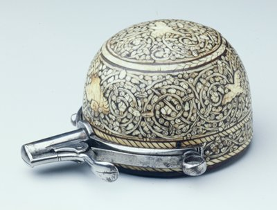 a dome of inlaid bone on wood with attached metal spout with retractable cover, a ring at each side to hang; dome decorated with birds and spiraling vines; flower at center of bottom.