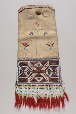 beaded panel with geometric design at bottom of bag; fringe with strung beads and red tassels; simple quillwork design of flowers on body of bag