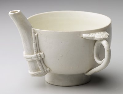 small tea bowl shape with looped handle covered with decorative element with circles; small spout attached to cup with ceramic coils; white glaze