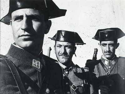 3 men wearing uniforms and shiny leather caps; 2 men at R have mustaches and gun barrels are visible behind their PR shoulders