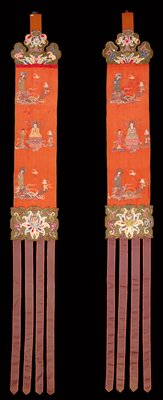 Banner, one of two (cf.25.363); red satin ground embroidered with three rows of figures, terminating at top in green satin scroll, set with mirror discs, and at bottom with scroll and four purple streamers reversible.