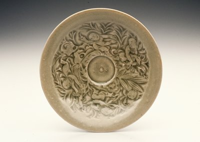 small green glazed plate with incised molded decoration of 5 boys and 2 dogs playing among plants