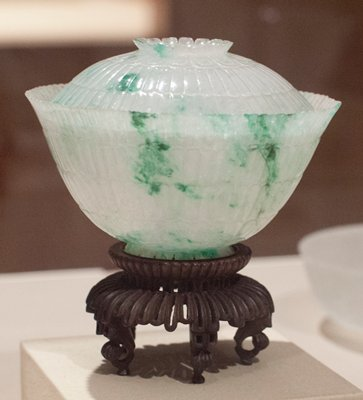 Bowl, one of a pair, covered fei t-sui jade carved in chrysanthemum form. This white jade, flecked with green called by the Chinese 'moss entangled in melting snow'. Carved inside and out in four rows of petal design. Small spreading base also carved in spread petal design. Extraordinarily fragile and brilliant. Pair with 34.21.6a,b