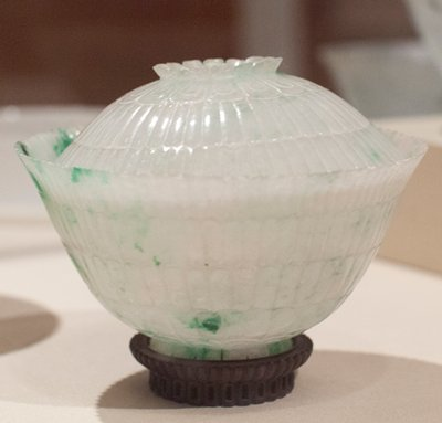 Bowl, one of a pair, covered fei t-sui jade carved in chrysanthemum form. This white jade, flecked with green called by the Chinese 'moss entangled in melting snow'. Carved inside and out in four rows of petal design. Small spreading base also carved in spread petal design. Extraordinarily fragile and brilliant. Pair with 34.21.5a,b