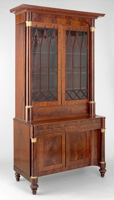 desk with drawer with felt-covered writing surface with storage below; double doors on bottom of desk; hutch with glass doors and tilt-up panel below with drawers and compartments; pairs of metal-capitaled columns on hutch and desk