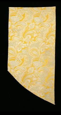 mustard yellow background; silver and green paisley, feather and foliate design on irregularly-shaped fragment