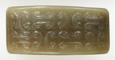 Semi-translucent grey jade marked with brown clouds. Used a decorative ring on belt.