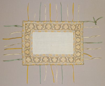 The front of a Pillow Slip in finest linen battiste, embroidered with pale lilac and gold colored silks in various stitches. Floral ornament in two narrow outer borders. Gold colored ornato with background of lilac embroidery. Tiny analogous colored silk ribbons are attached to edges, serving to attach upper to under pillow slip.
