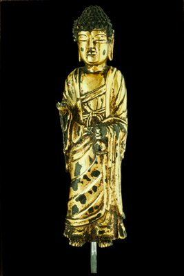 gilt-bronze Buddha; one hands holds holy water bottle, other is damaged; meant to be seen from front, back has three open rectangles (gilt chipped at lower half)
