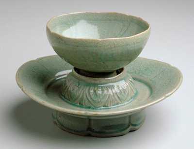 cup and footed saucer on lotus flower platform which holds lotus-shaped cup; underglazed floral patterns on both cup and saucer