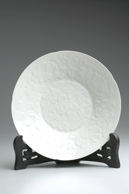 Scalloped edge dish; raised decoration throughout interior of flowers and foliage; white glaze overall