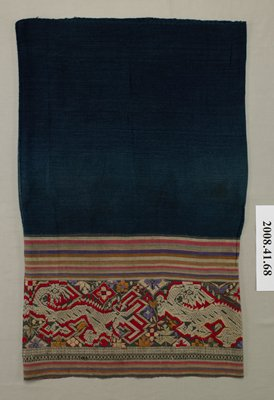 indigo colored skirt with a wide band of striped fabric attached at bottom; stripe colors: tan, red, orange, purple and green; stripe panel is embroidered with three dragons and floral motifs; band of tan geometric designs below dragon panel