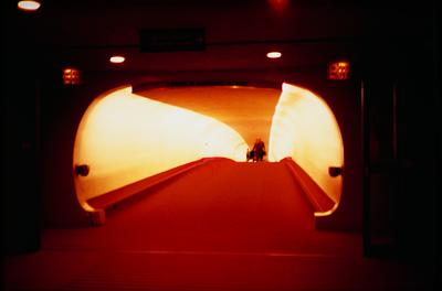 blurry image of a small group of people with luggage emerging from a slope tunnel; light has orange cast within tunnel; exit sign at UR and UL