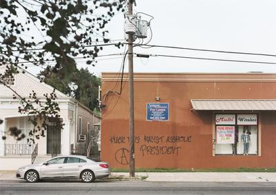 """color image of street scene; white house on L with black metal railing around porch and stairs to front door; orange building on R with advertisement signs for """"Multi Wireless"""" and two mannequins in window, as well as a blue """"For Lease"""" sign at center, over black graffiti that reads: """"Fuck this racist asshole president""""; silver sedan parked on street in foreground"""