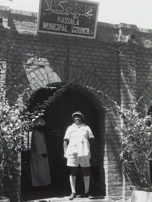 "Black and white photograph of a man wearing white standing in an arch under a sign that says ""Kassala Municipal Council"""