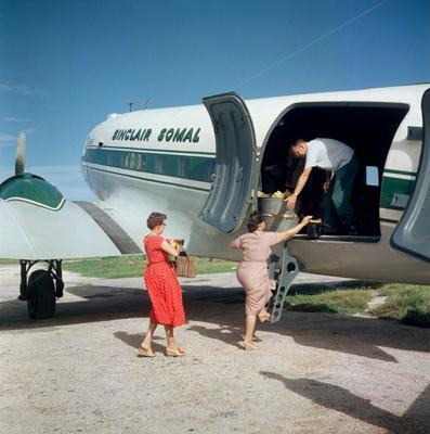 Color photograph of a man helping two woman onto a white and green airplane