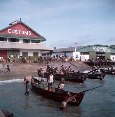 Color image of a shipping yard; two buildings in background with boats with figures in them in the foreground