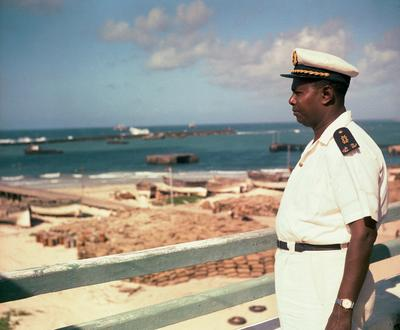 Color image of a man in a white uniform looking to the viewer's left; teal body of water in the background