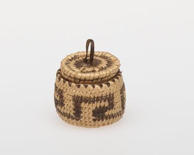 Miniature round basket with cover; coiled. Design consists of a simple fret around sides. Cover has red spots. Colors are natural, red and black.