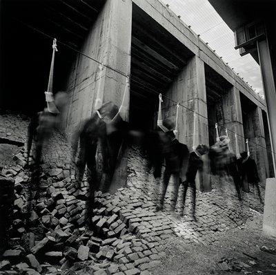 several cut-outs of figures swinging by nooses beneath a bridge