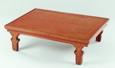Low red lacquer table with organic shaped legs; gold inlay in floral designs on edge of tabletop, apron and on legs